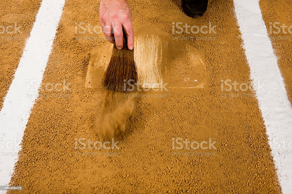 Baseball umpire cleaning home plate. Play Ball stock photo