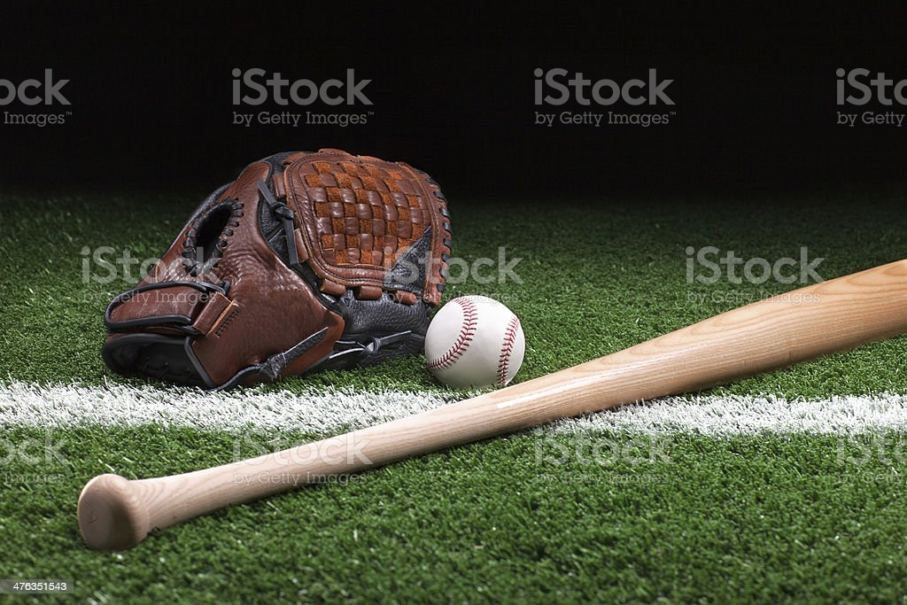 Baseball with mitt and bat on green grass at night stock photo