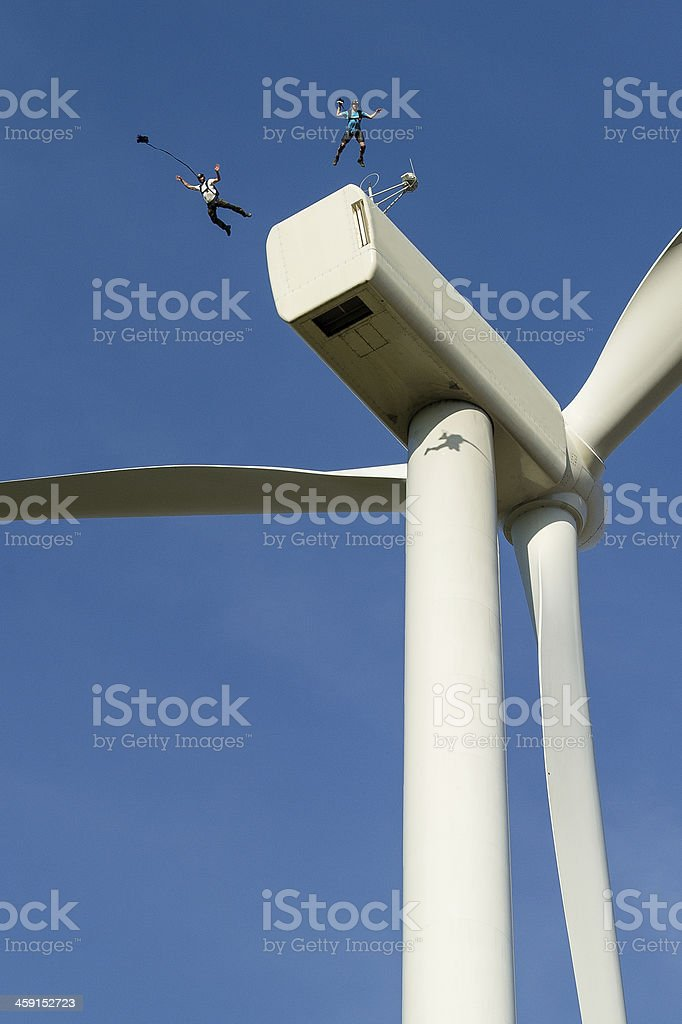BASE-jumpers leaping off a wind turbine stock photo