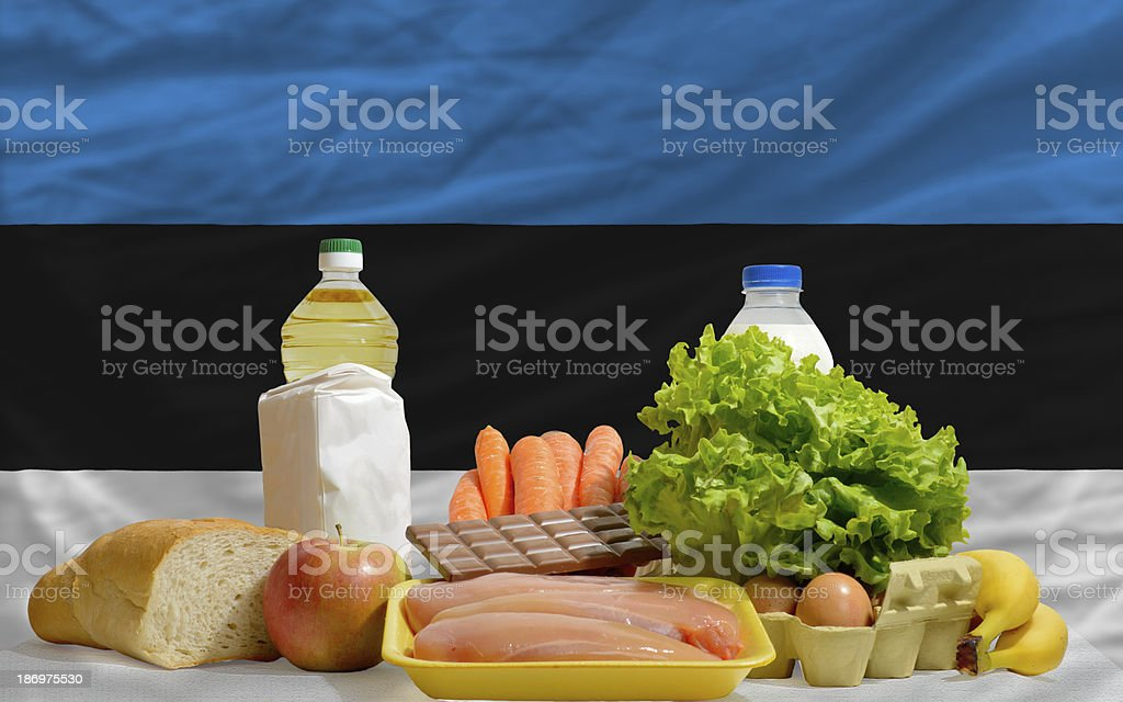 basic food groceries in front of estonia national flag stock photo