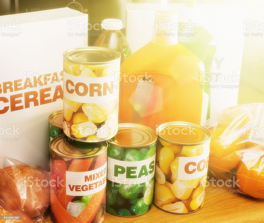 Basic generic packaged and fresh foods in sunlit home kitchen stock photo