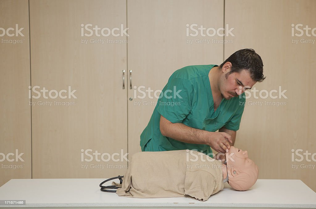 Basic life support training with a CPR Dummy-opening airway royalty-free stock photo