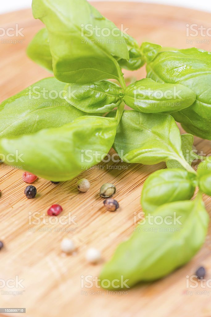 Basil leafs and pepper corn on wooden cutting board stock photo