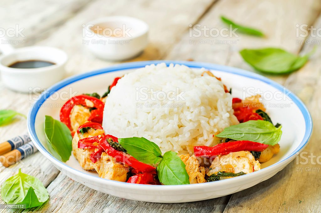 Basil pepper chicken stir fry with rice stock photo