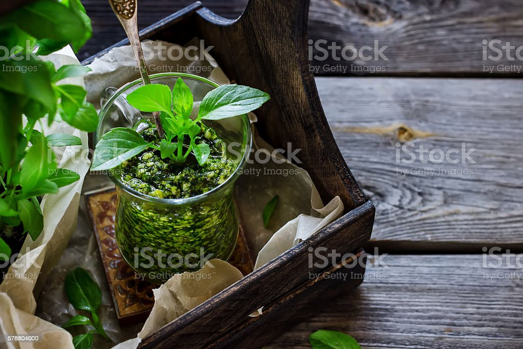 Basil pesto sauce in glass on wooden table. stock photo