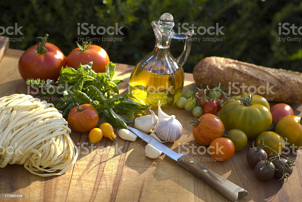 Basil, Vegetables & Spaghetti Pasta Dinner Cooking Preparation on Cutting Board royalty-free stock photo