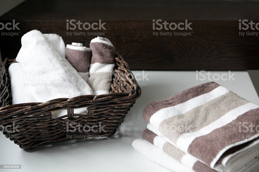 Basket and stack of terry cloth towels in bathroom stock photo
