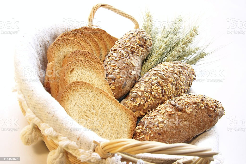 Basket full of fresh bread loaves and slices royalty-free stock photo