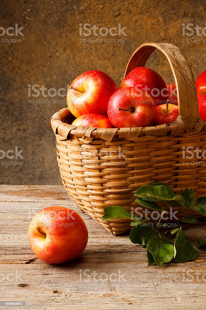 Basket full of red apples on a wooden surface stock photo