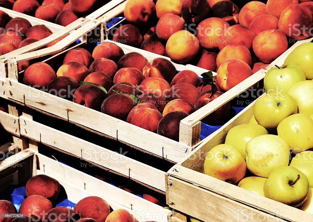 basket of apples and peaches for sale at market fruit stock photo