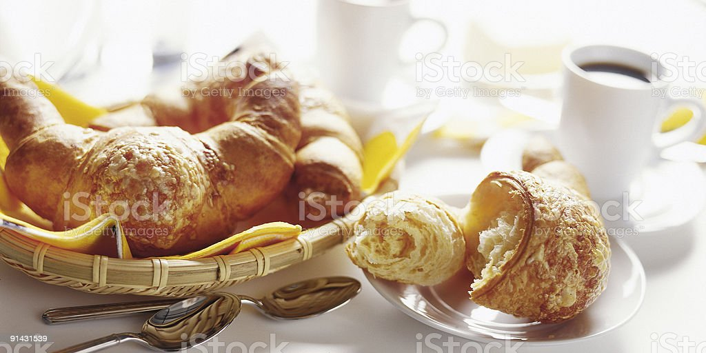 Basket of breakfast croissants with black coffee stock photo