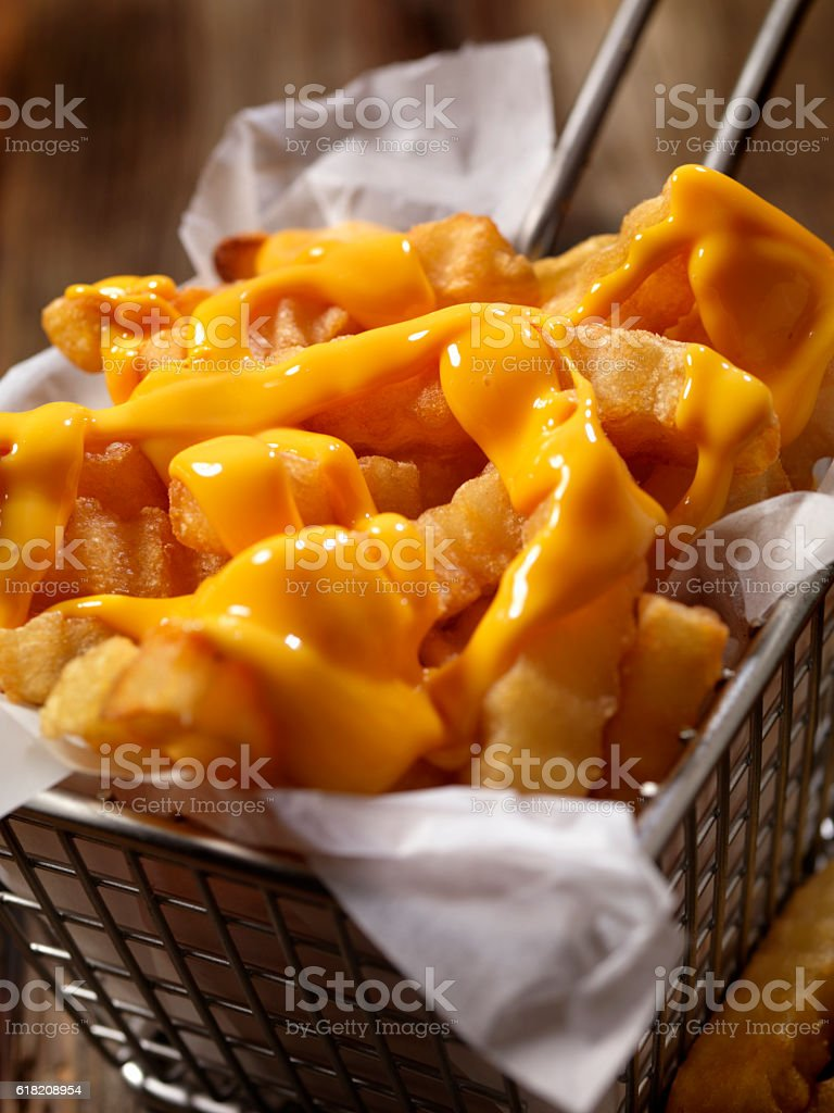 Basket of Cheesy Crinkle Cut French Fries stock photo