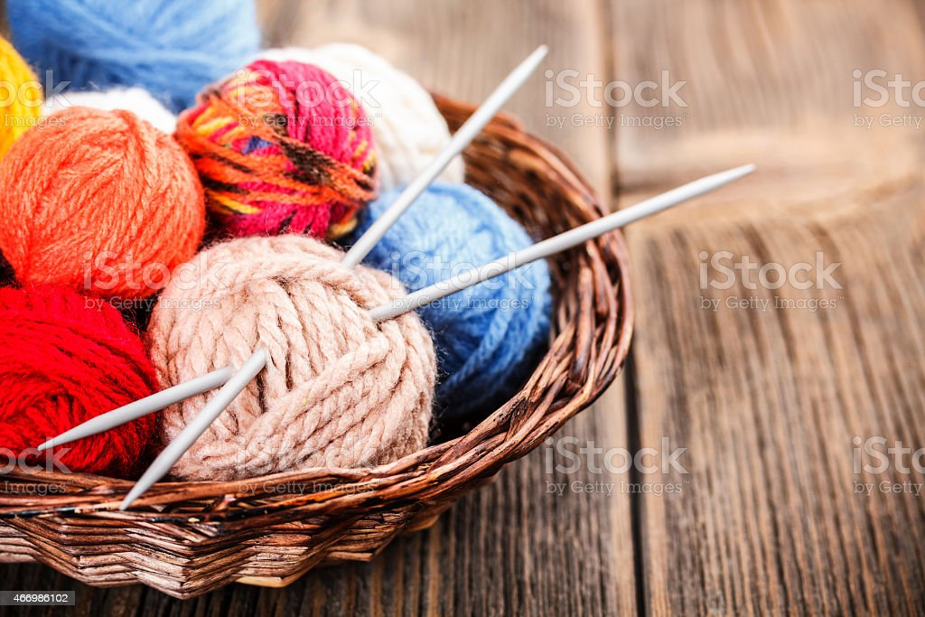 A basket of colored knitting yarn balls with pair of needle stock photo