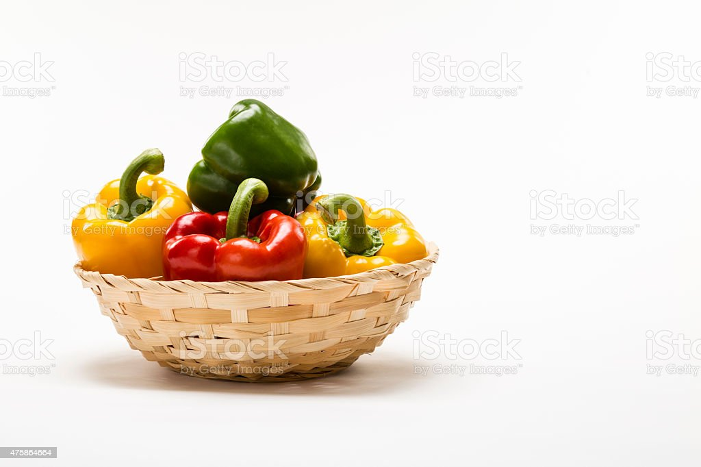 Basket of colorful Bell Peppers on white background. stock photo
