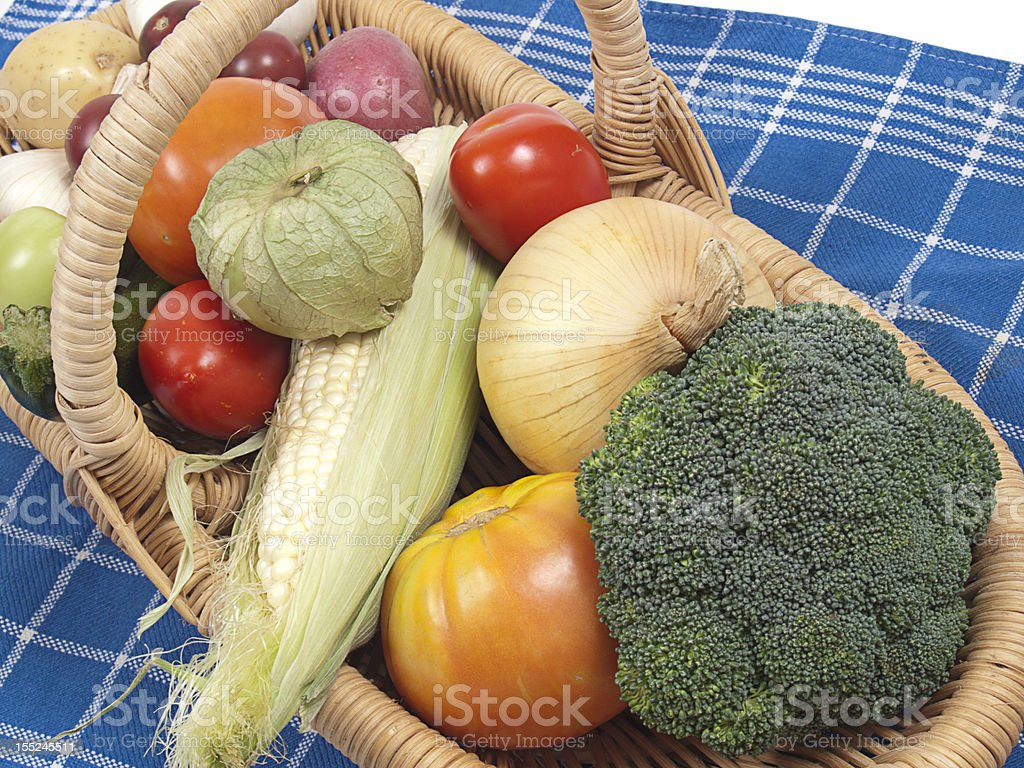 Basket of fresh raw vegetables on a blue checkered cloth stock photo