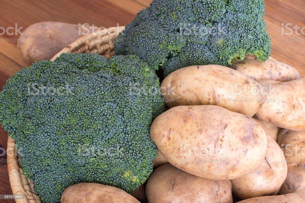 Basket of potatoes and broccoli stock photo