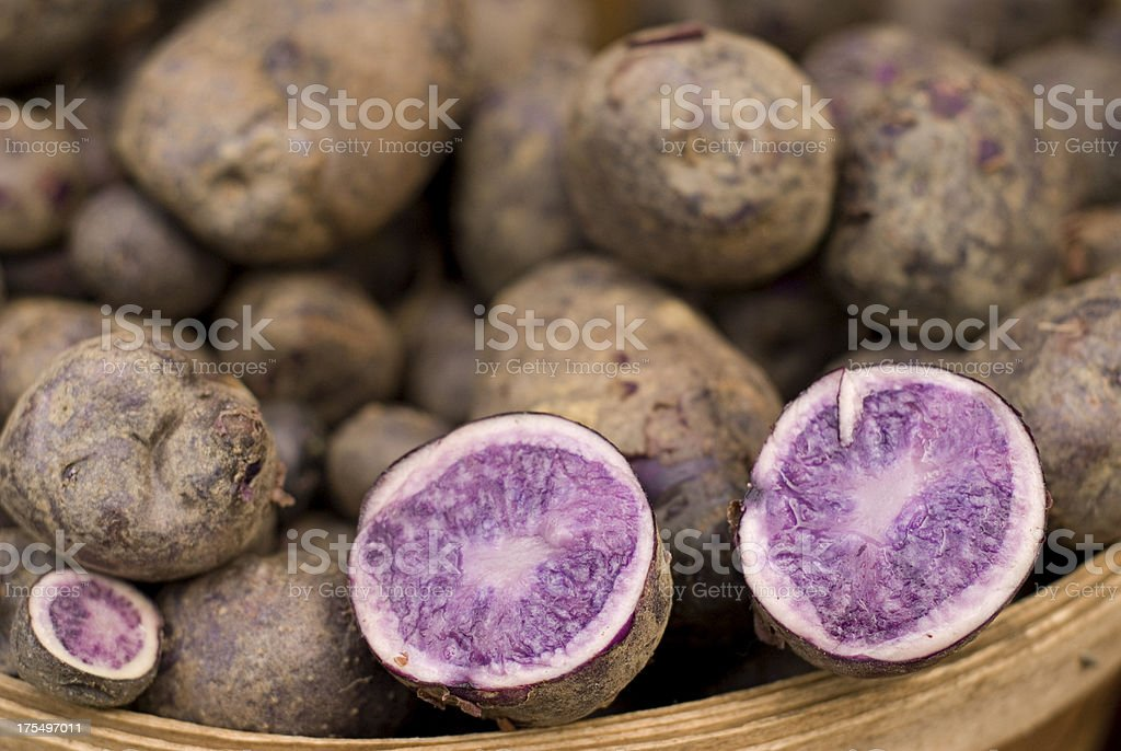 Basket of Purple Potatoes With One Cut Open stock photo