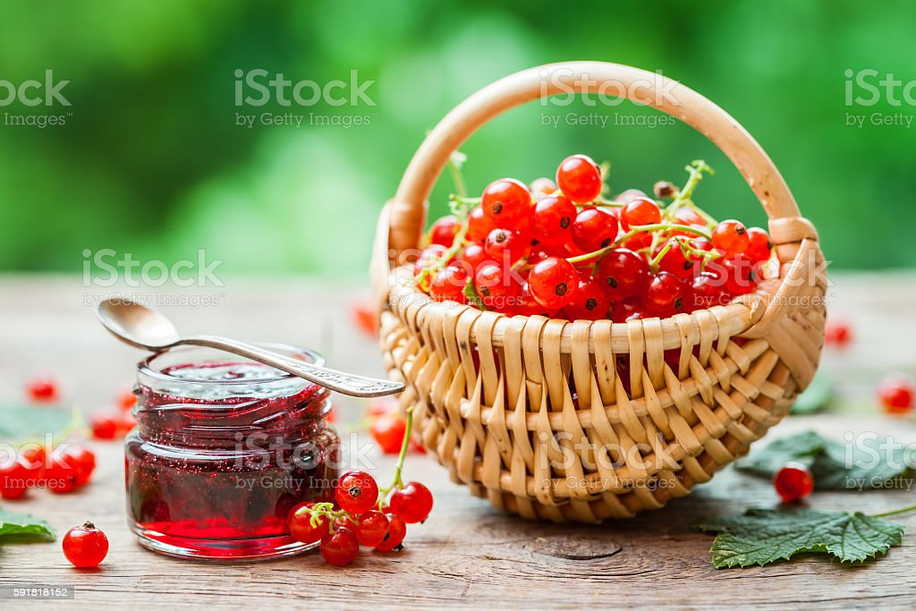 Basket of Red currant berries and jar of redcurrant jam stock photo