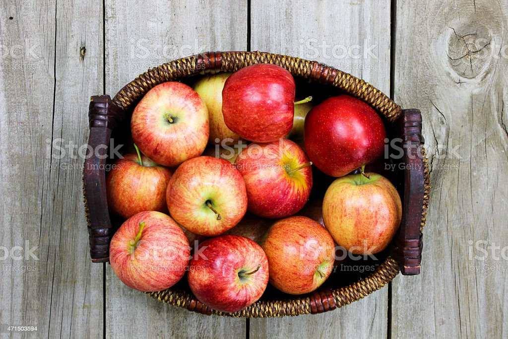 Basket of red gala apples on wood table stock photo