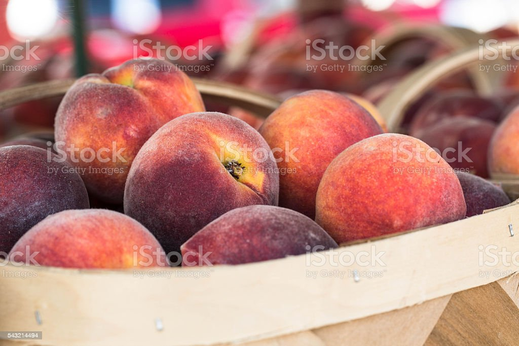 Basket of Ripe Peaches at Farmers Market stock photo