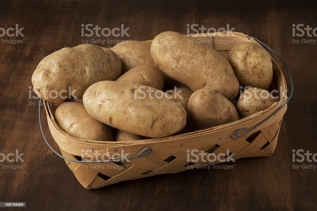 Basket of Russet Potatoes on a Table stock photo