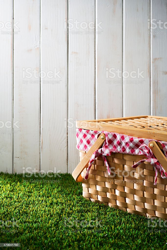 Basket Sitting on Green Grass with White Fence stock photo