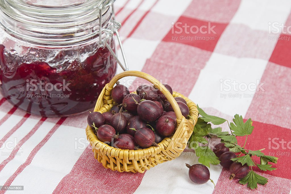 Basket with berries of a red gooseberry and jam royalty-free stock photo