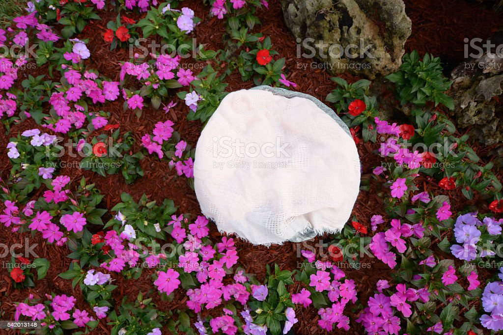 Basket with fabrics surrounded by purple flowers stock photo