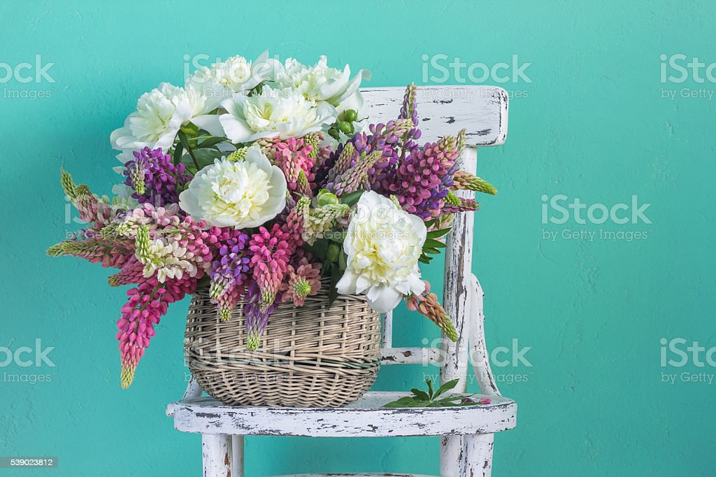 Basket with flowers peonies and lupins stock photo