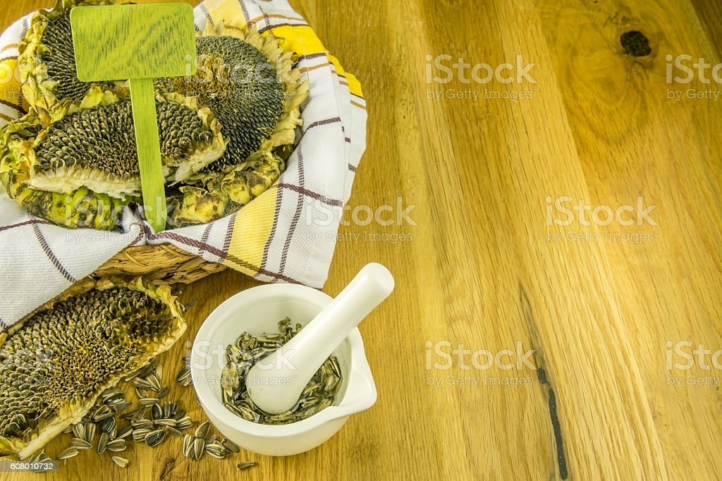 Basket with sunflowers and mortar with crushed seeds stock photo