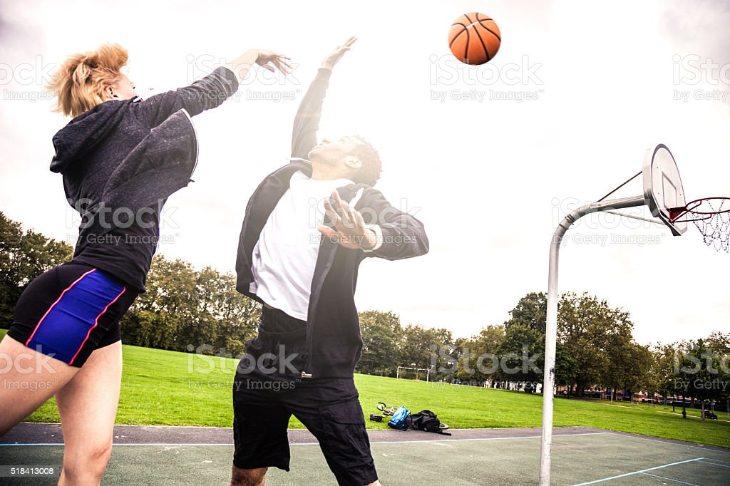 Basketball 1v1 man-woman in a London playground stock photo