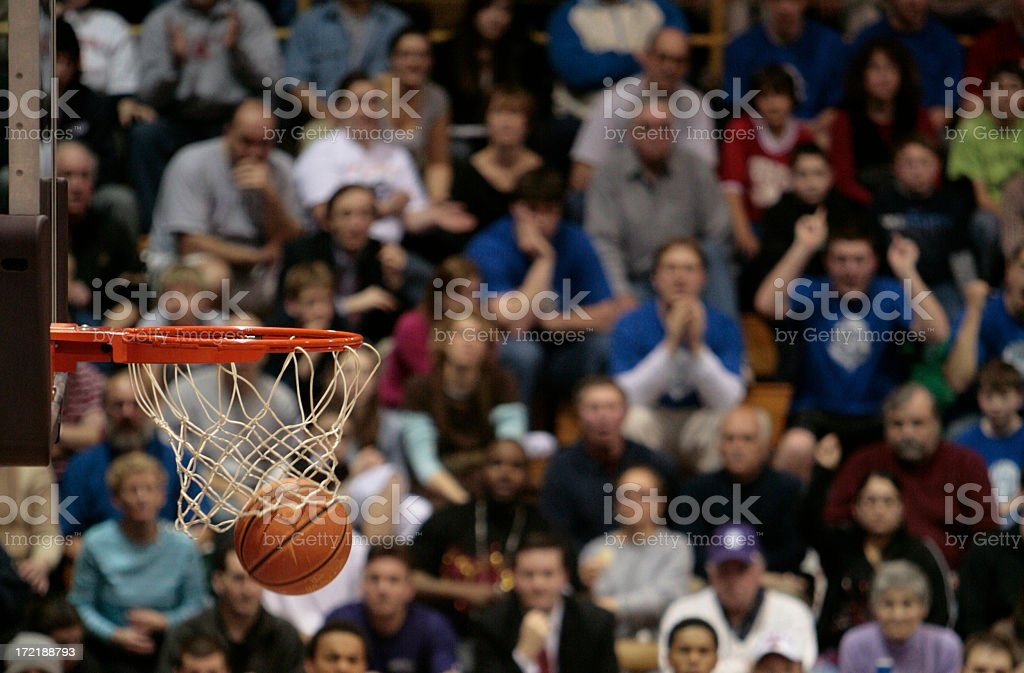 Basketball ball and backboard with fans in the background. stock photo