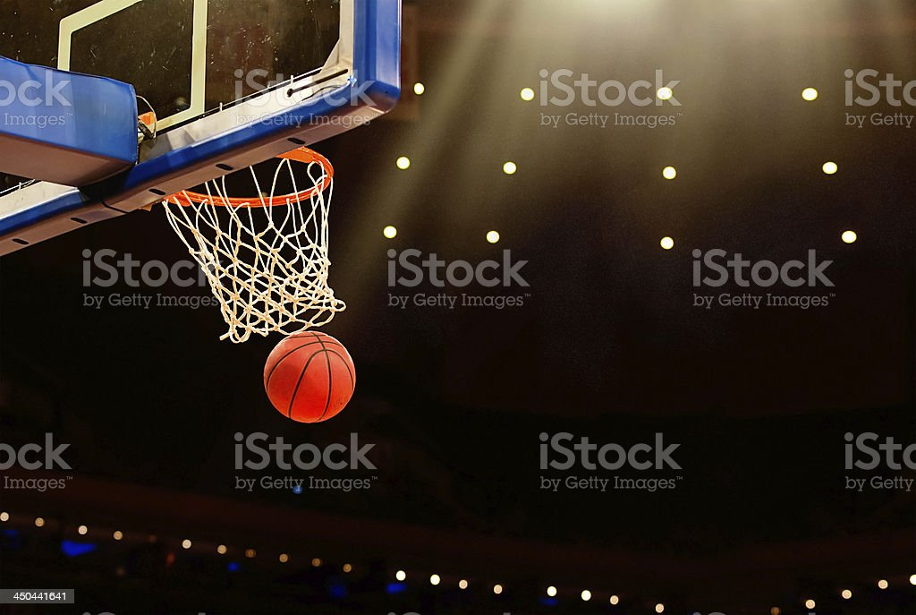 Basketball basket with ball going through net stock photo