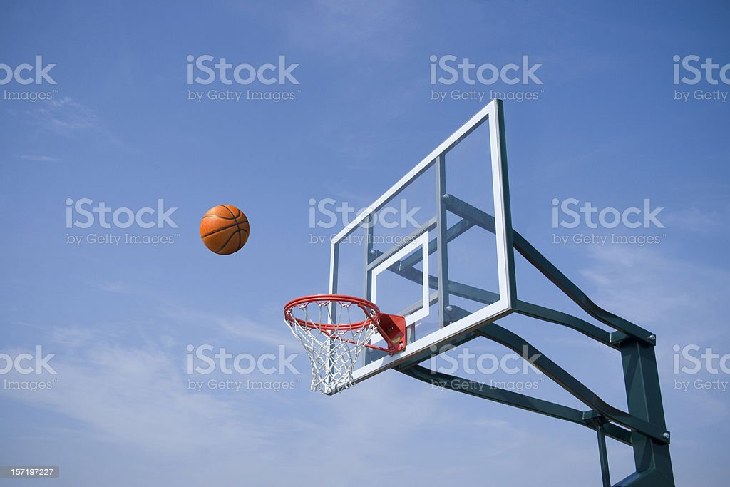 A basketball bring thrown into a hoop royalty-free stock photo