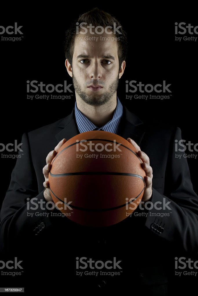 basketball coach (businessman) in suit holding ball (low-key studio shot) royalty-free stock photo
