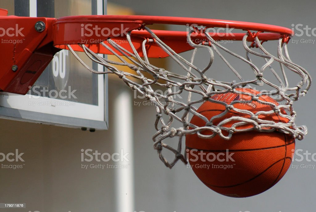 A basketball dropping through a net stock photo