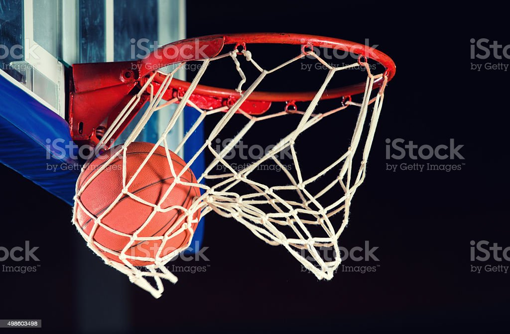 Basketball entering the hoop. stock photo