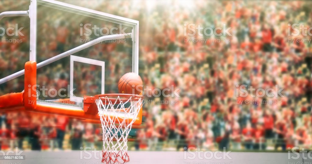 Basketball going through net and scoring during match ,Blurry and soft focus stock photo