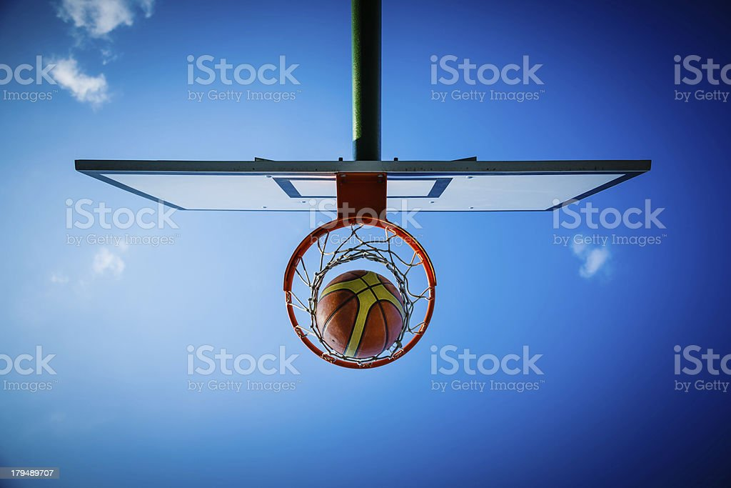 Basketball hitting in hoop with net royalty-free stock photo