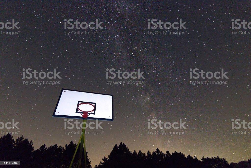 Basketball hoop and board under starry night. Milky way galaxy stock photo