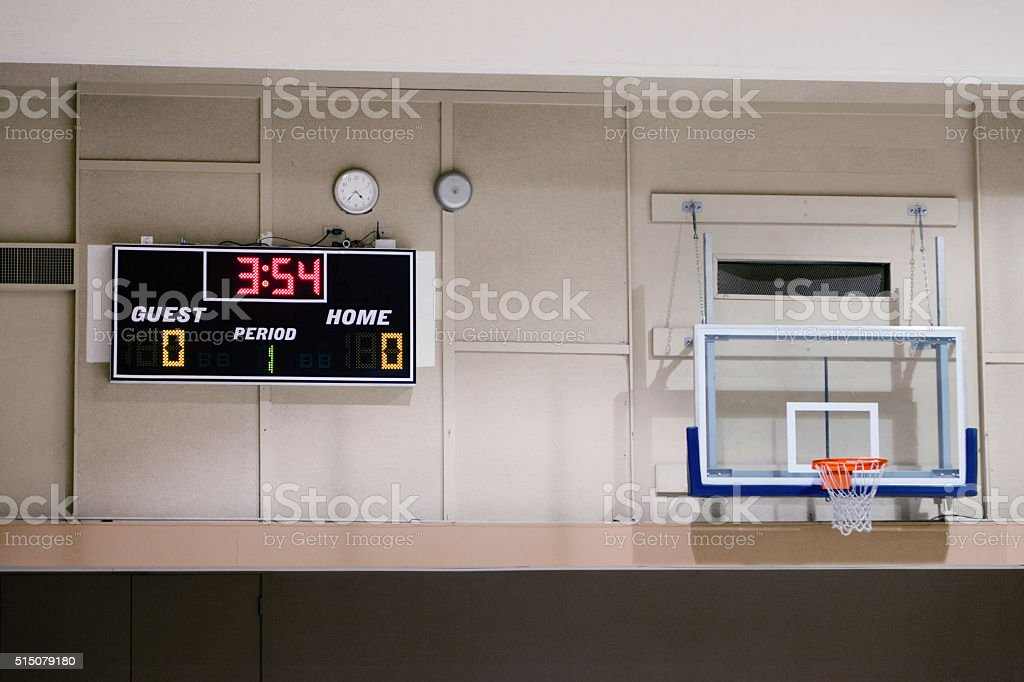 Basketball hoop and scoreboard in a school gym stock photo