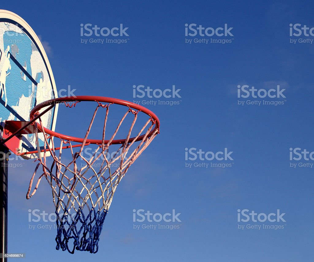 Basketball hoop, net and backboard against blue sky stock photo