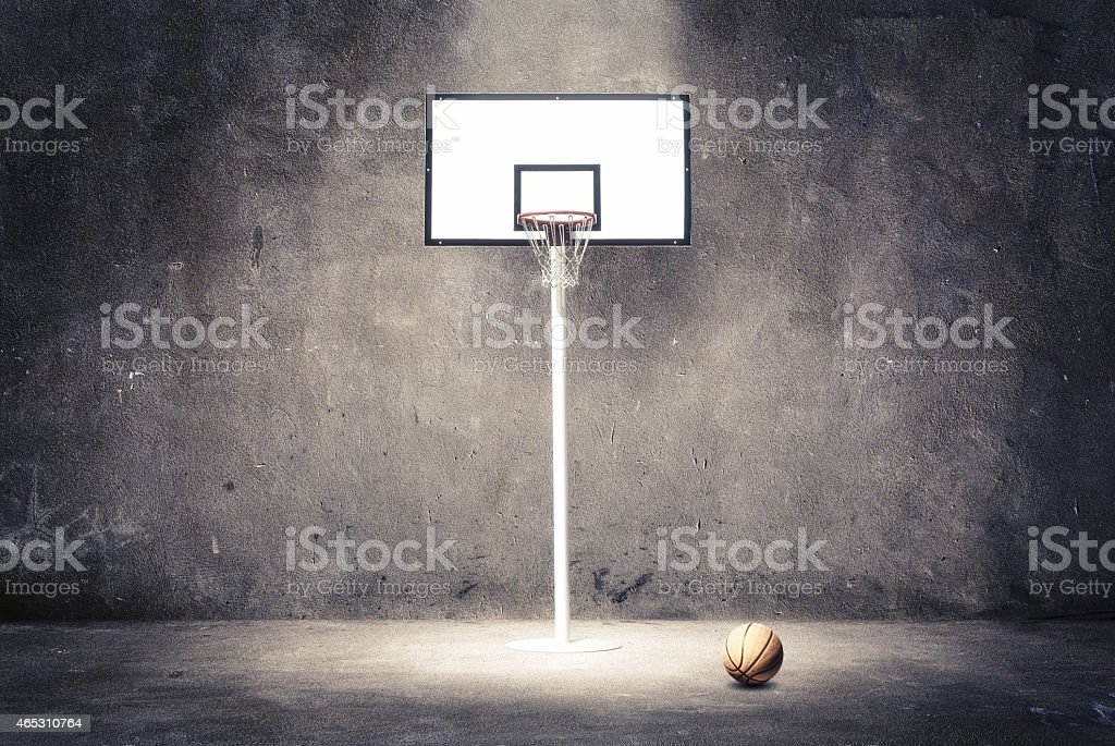 Basketball hoop on a textured wall with a ball. stock photo