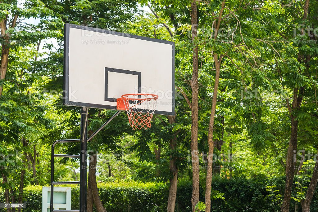 Basketball hoop with green trees on background. stock photo