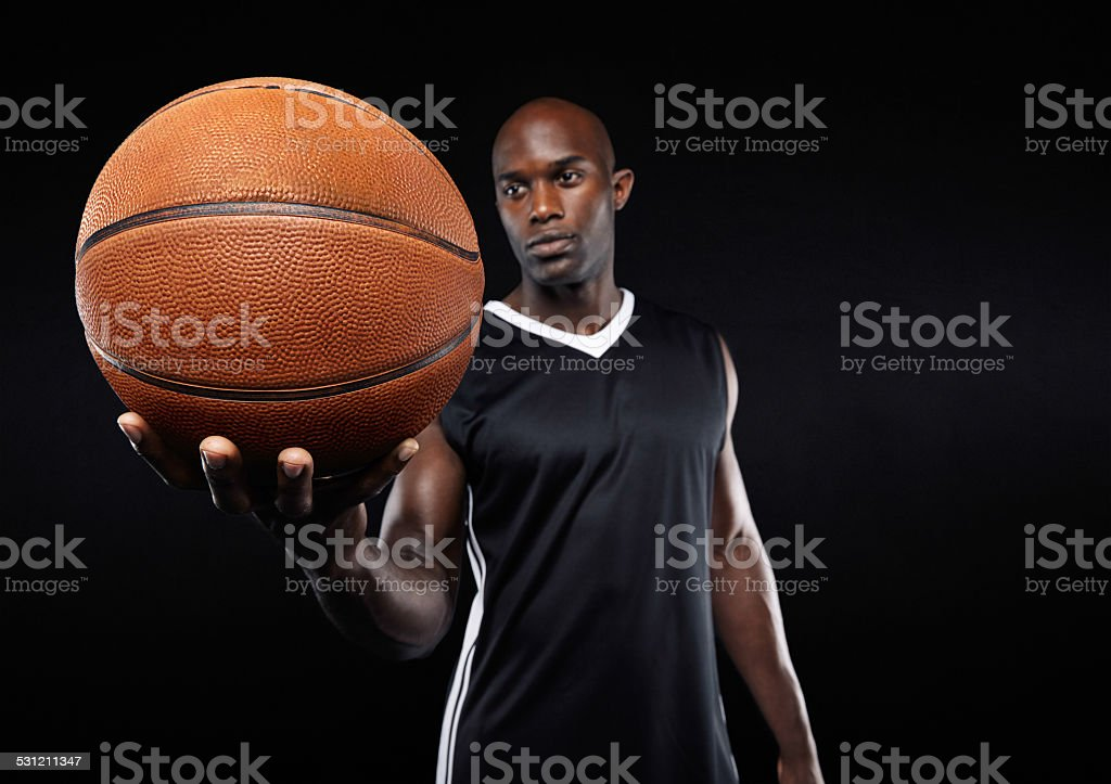 Basketball in hand of african sportsman stock photo