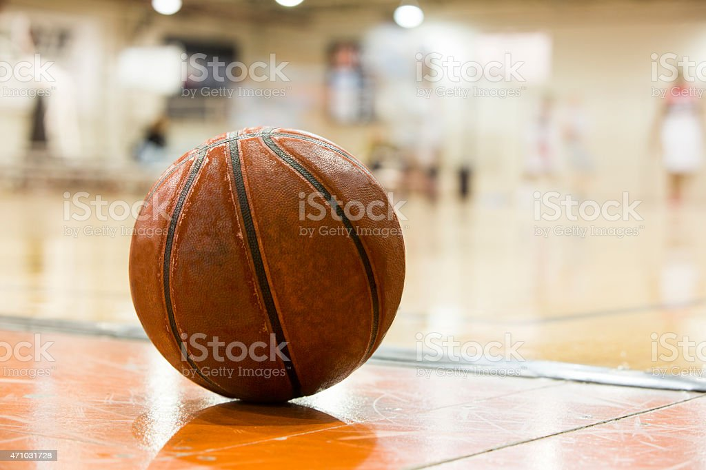 A basketball in the middle of a court stock photo