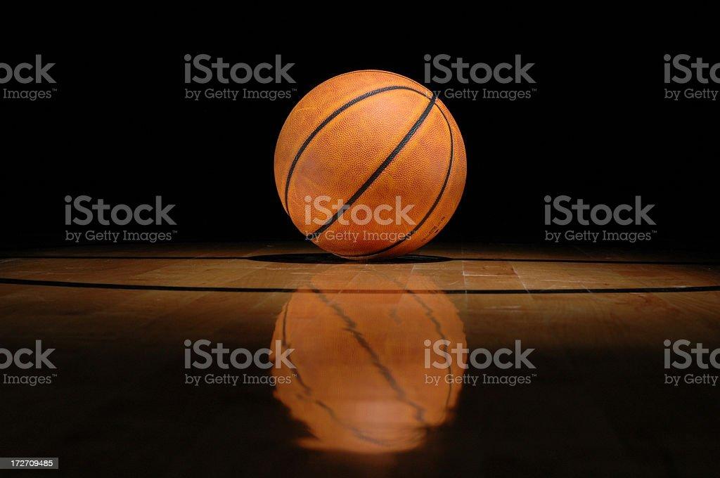 Basketball lying on shiny court against black background stock photo