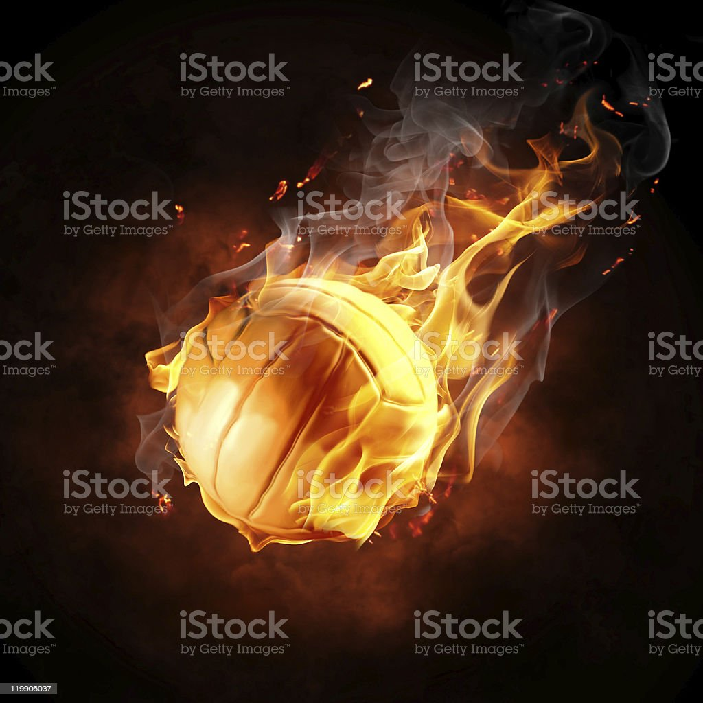Basketball on fire against black backdrop stock photo