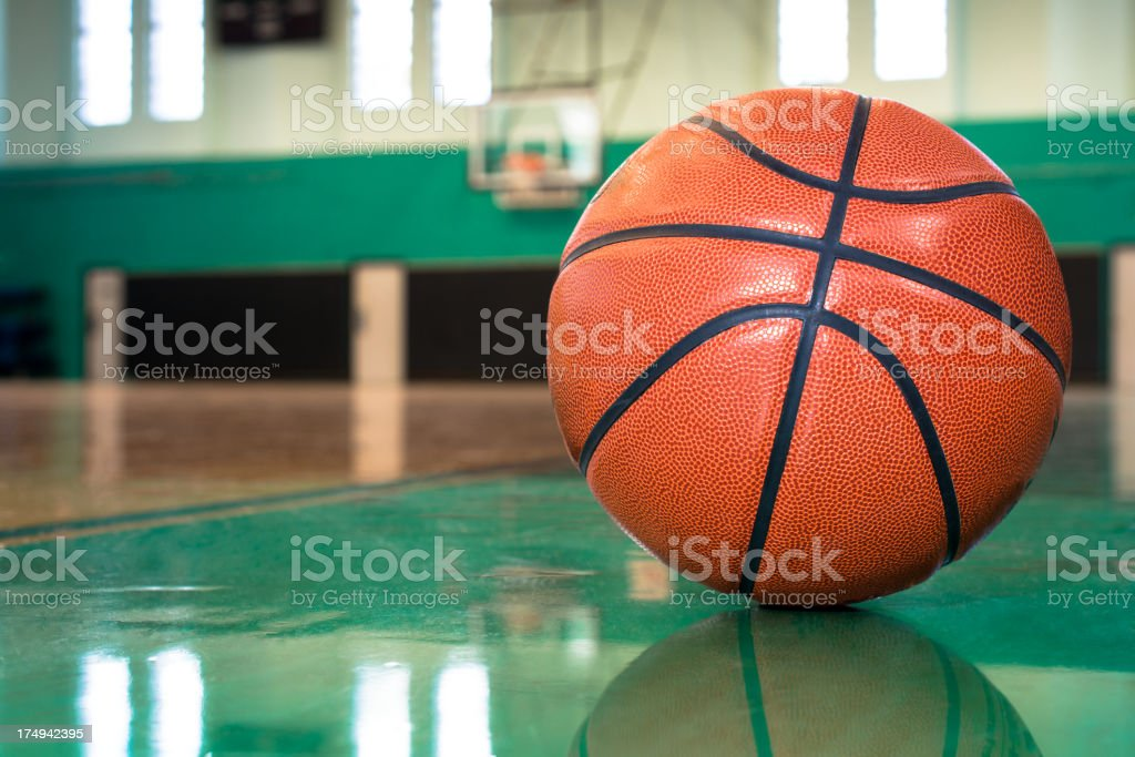 Basketball on Worn Old Wooden Court Floor royalty-free stock photo