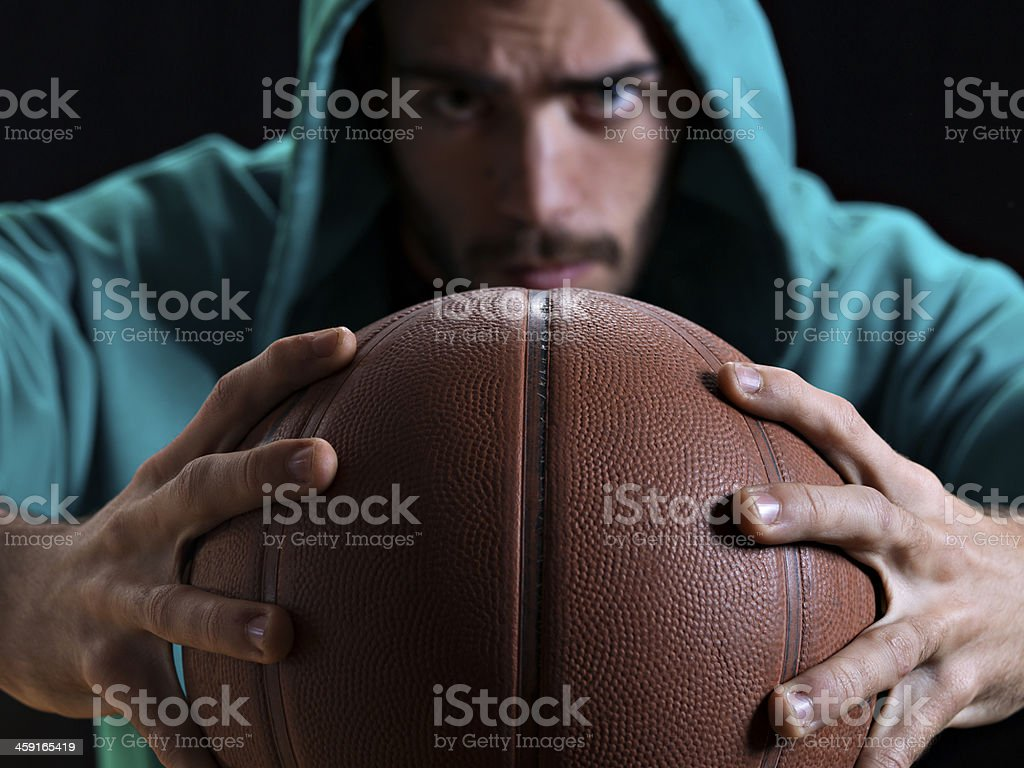 closeup of a basketball with a rapper at the background